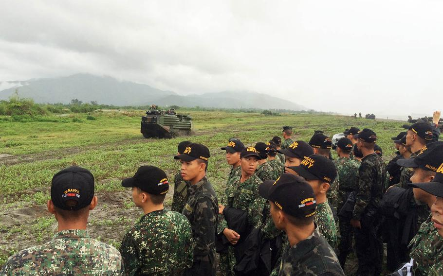 Filipino sailors watch U.S. and Philippine Marines in amphibious-assault vehicles land on a beach last year in Luzon, Philippines.