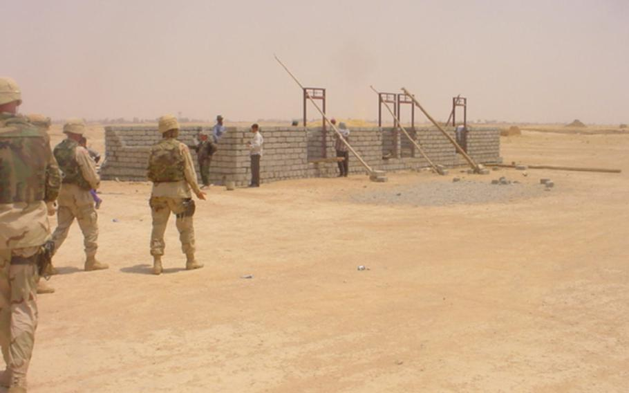 American soldiers are pictured visiting a school under construction in the village of Jeddalah, near Qayara Airfield West, in this photo dated Monday, July 7, 2003.