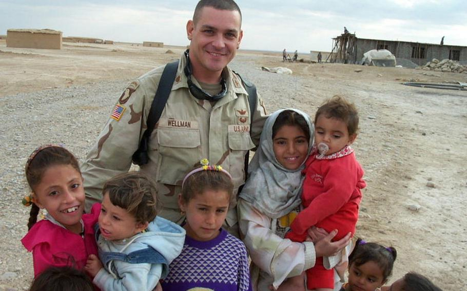 Pictured here on November 13, 2003, Fred Wellman, then a major in the U.S. Army's 101st Airborne Division combat aviation brigade, poses with the children of Jeddalah village near Qayara Airfield West, about 40 miles south of Mosul.