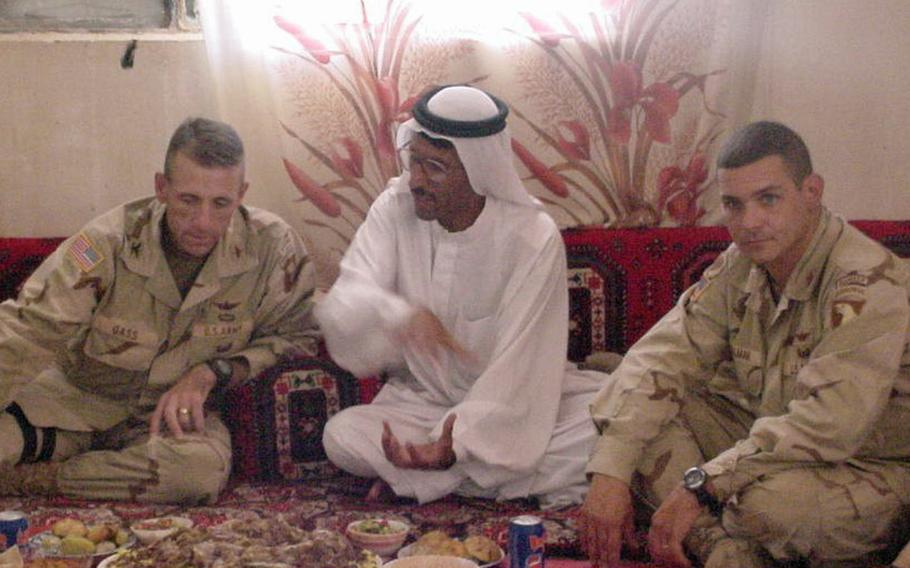 Pictured here sharing a meal in Jeddalah sometime in 2003 are, left to right, Col. Gregory Gass, Dr. Mohammed Ismail and Maj. Fred Wellman. Wellman said meals like this defined the Iraq War experience more than ''kicking down doors.''
