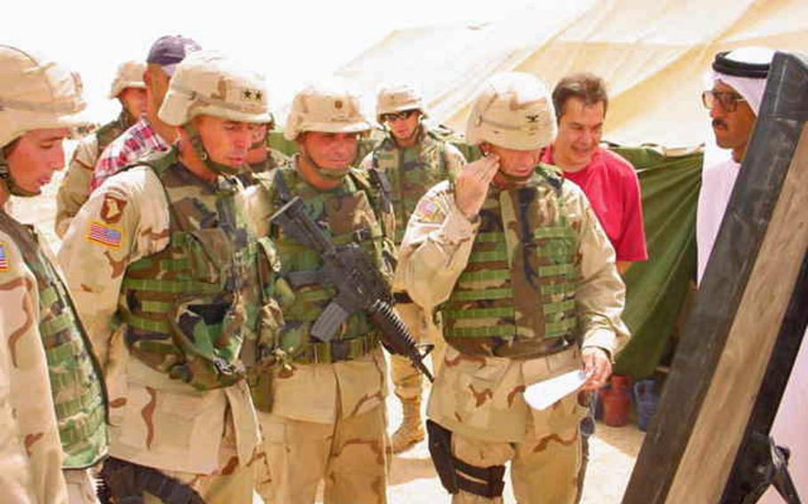 Then-Maj. Gen. David Petraeus is briefed by then-Maj. Fred Wellman, middle, and then-Col. Gregory Gass, right, on a visit to the village of Jeddalah on Thursday, July 10, 2003. Dr. Mohammed, the village sheikh and doctor, is in white on the far right.