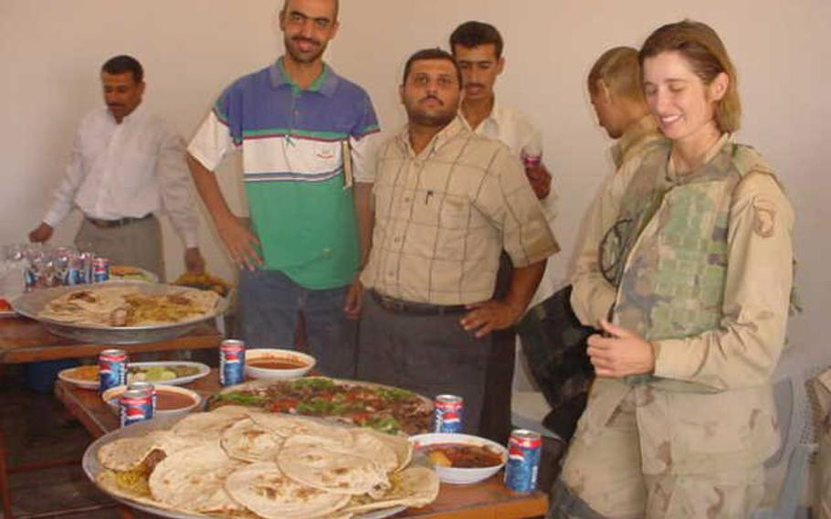 Pictured at a lunch in this undated photo from Fred Wellman's collection are Iraqi translators Bassam Sabry, left in green and blue, and Osama Saado to his right with then-Capt. Kellie Rourke on the far right.