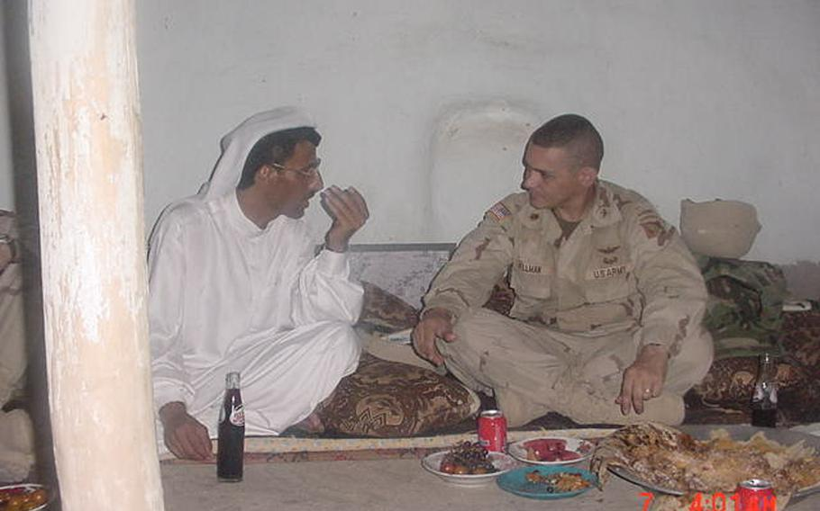 Dr. Mohammed Ismail and then-Maj. Fred Wellman share one of their earliest meals together in Jeddalah, shortly after U.S. troops occupied nearby Qayara Airfield West, in this undated photo from 2003. Mohammed would go on to become an important partner in U.S. reconstruction efforts in the area.