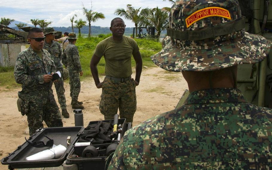 Gunnery Sgt. Troy Telford with Amphibious Assault Company, Combat Assault Battalion, 3rd Marine Division, discusses Assault Amphibious Vehicle procedures before embarking onto the Philippine navy's BRP Tarlac during exercise Kamandag in Subic Bay, Philippines, Oct. 3, 2017.