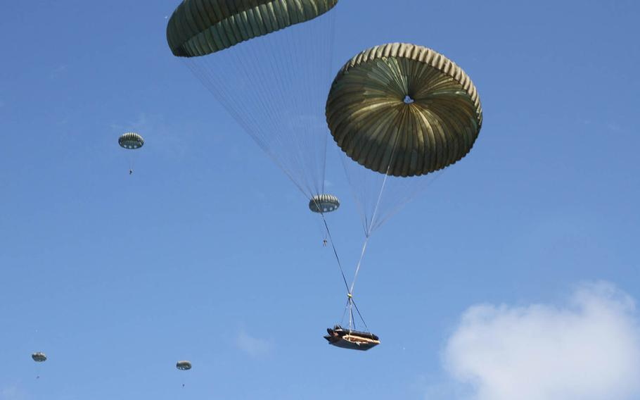 Marines from 3rd Reconnaissance Battalion, 3rd Marine Division descend, along with a Combat Rubber Raiding Craft, toward the sea after jumping from a C-130 off Okinawa's east coast, Wednesday, Oct. 11, 2017.