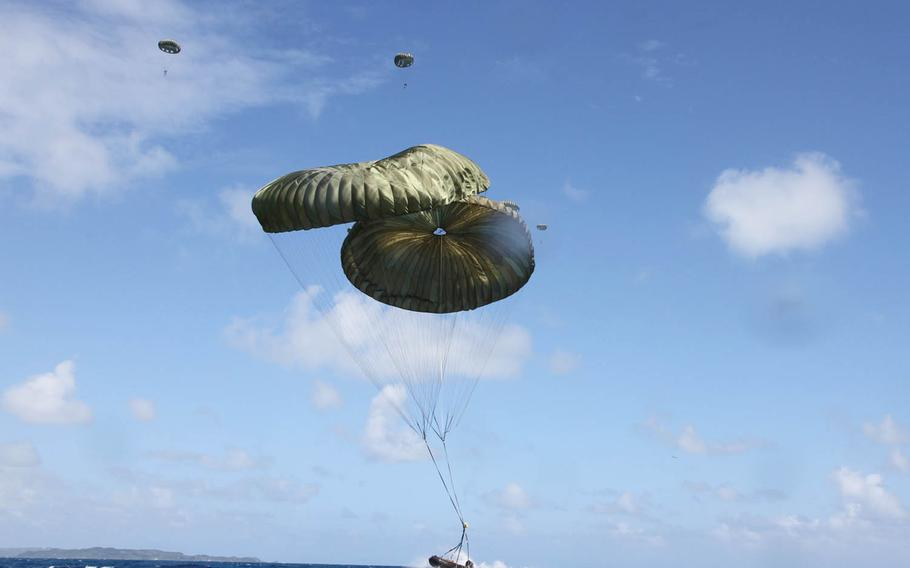 A Combat Rubber Raiding Craft falls onto the sea off Okinawa's eastern coast as Marines from 3rd Reconnaissance Battalion, 3rd Marine Division, descend in the background, Wednesday, Oct. 11, 2017.