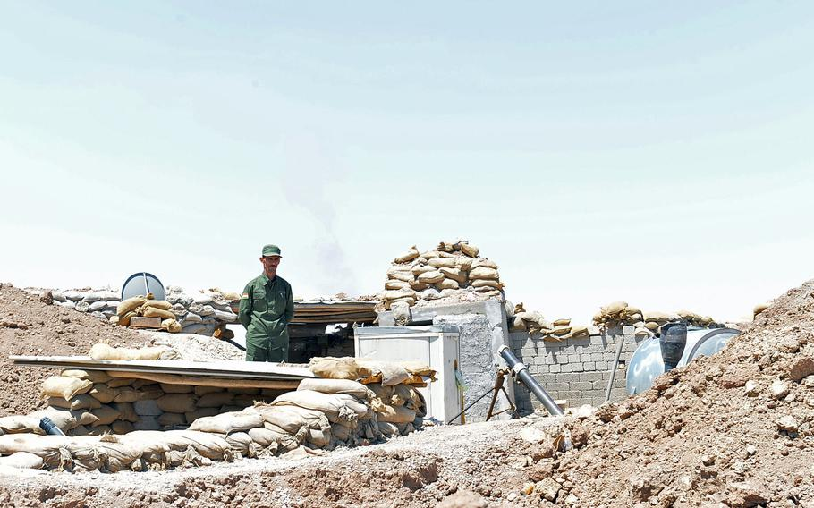 A peshmerga fighter stands on the berm at the Kurdish front lines about 15 miles from Islamic State-occupied Mosul on July 14, 2016. Troops here are among the closest Kurdish forces to Iraq's second-largest city and the militants' last urban stronghold in Iraq.