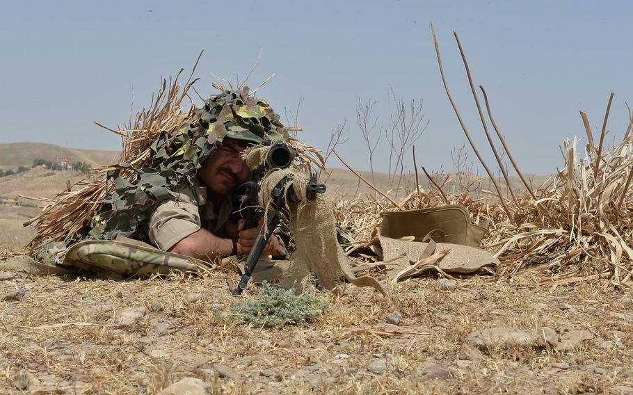 A Kurdish sniper sights in on a target during an exercise at a training site outside Irbil, the capital of Iraq's Kurdish region, on July 26, 2016. The exercise was the culmination of a training program to prepare peshmerga fighters for combined arms operations with snipers and artillery supporting infantry troops.