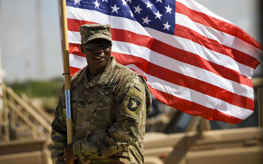 Army Staff Sgt. Anthony Miller with the 101st Airborne Division holds the American flag during a graduation ceremony for Somali National Army soldiers in Mogadishu, Somalia, May 24, 2017.