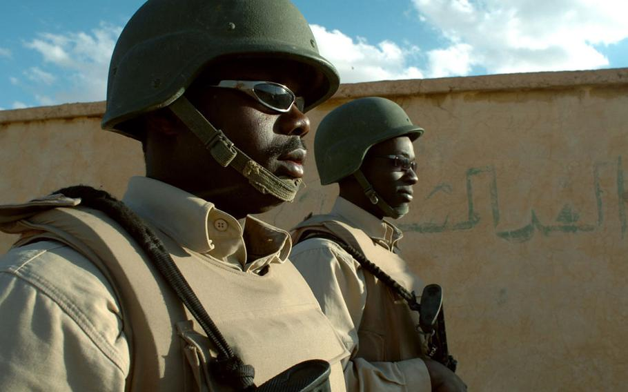 Matia Tibenda, and Alvin Ochieng, Ugandan contractors, do a roving patrol during a guard shift at Al Asad Air Base, Iraq, in 2006. Contractor Triple Canopy has agreed to pay a $2.6 million settlement to resolve claims that they billed the military for unqualified security guards at Al Asad Air Base in Iraq.