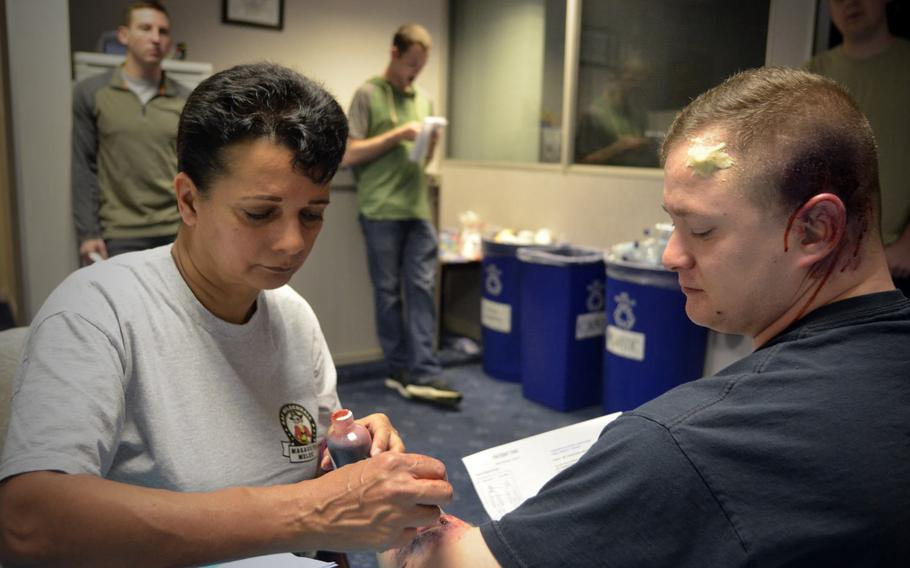 Karen Abeyasekere from the 100th Air Refueling Wing public affairs office applies a fake wound on U.S. Air Force Staff Sgt. David Davis before an active-shooter exercise at RAF Mildenhall, England, Wednesday, Oct. 18, 2017.