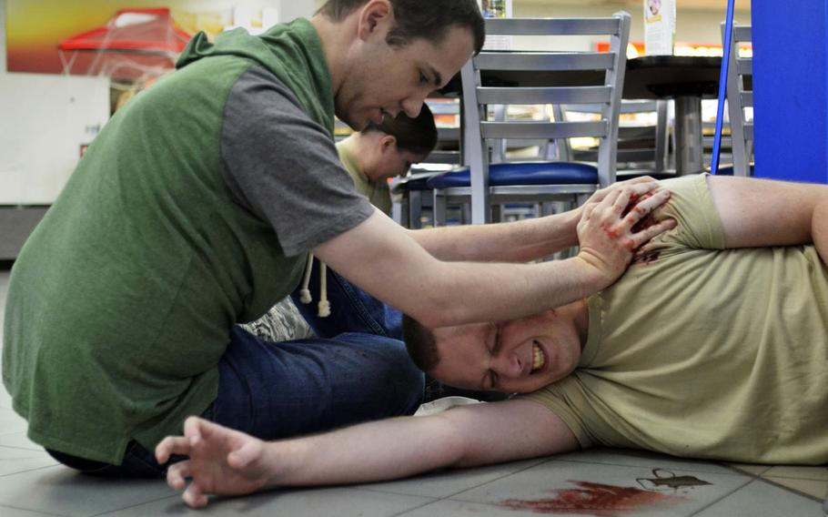 Airmen acting as simulated casualties try to stanch blood loss from gunshot wounds during an active-shooter exercise at RAF Mildenhall, England, Wednesday, Oct. 18, 2017.