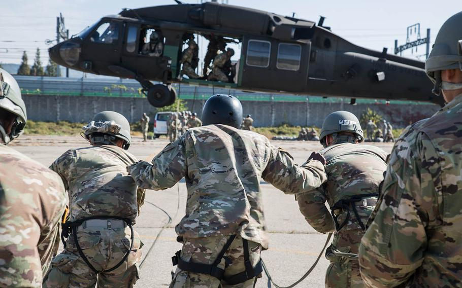 An air-assault instructor keeps two students from being blown away by rotor wash at Camp Mobile, South Korea, Thursday, Oct. 19, 2017.