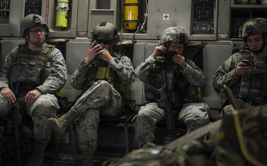 Airmen check their cellphones during a flight aboard a C-17 Globemaster III on Jan. 13, 2014. NATO's long-standing advantage in air, at sea and on land could be put at risk as highly skilled cyber adversaries probe for weaknesses.