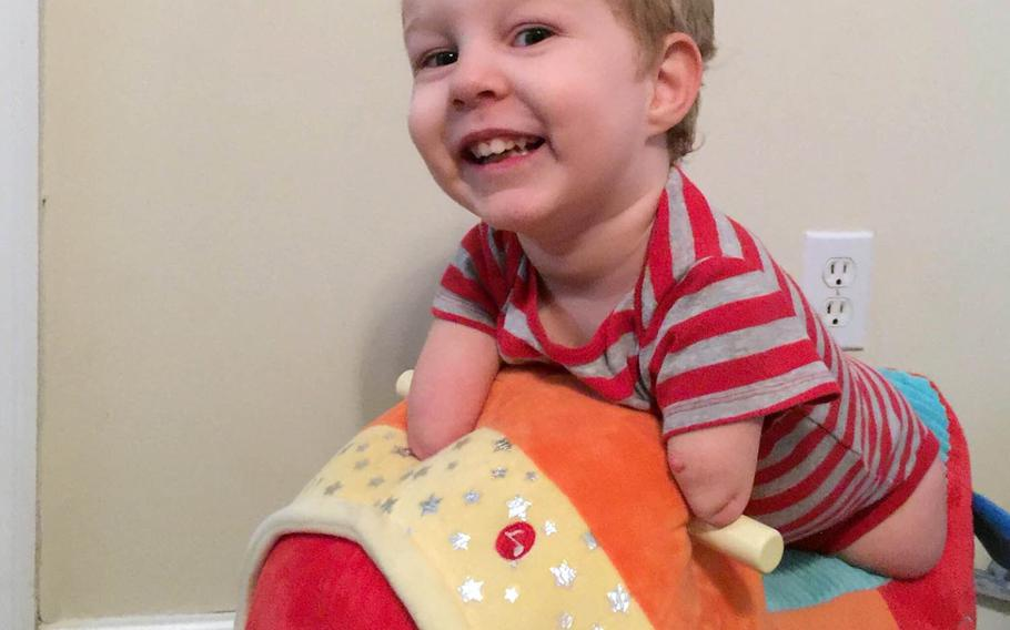 Camden Whiddon, 3, smiles while playing at home in Denton, Texas. Camden, whose family has links to the U.S. military in Japan, was born without forearms and legs.