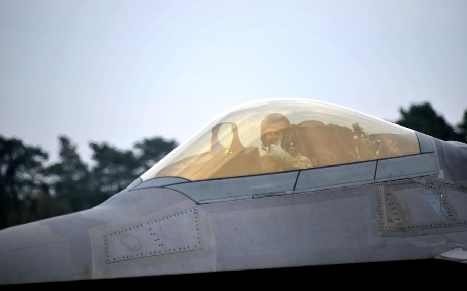 U.S. Air Force pilot of the 1st Fighter Wing signals from an F-22 Raptors while taxing towards the flight line before take-off at RAF Lakenheath, England, Thursday, October 19, 2017. Airmen of the 94th Fighter Squadron arrived earlier this month for air training missions.