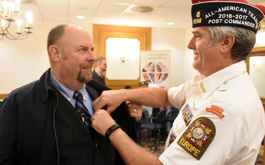 VFW Tower Post 10692 commander James Joyce, right, pins a Vietnam veteran lapel pin onto Jim Winslow in Grafenwoehr, Germany, Tuesday, Oct. 24, 2017.