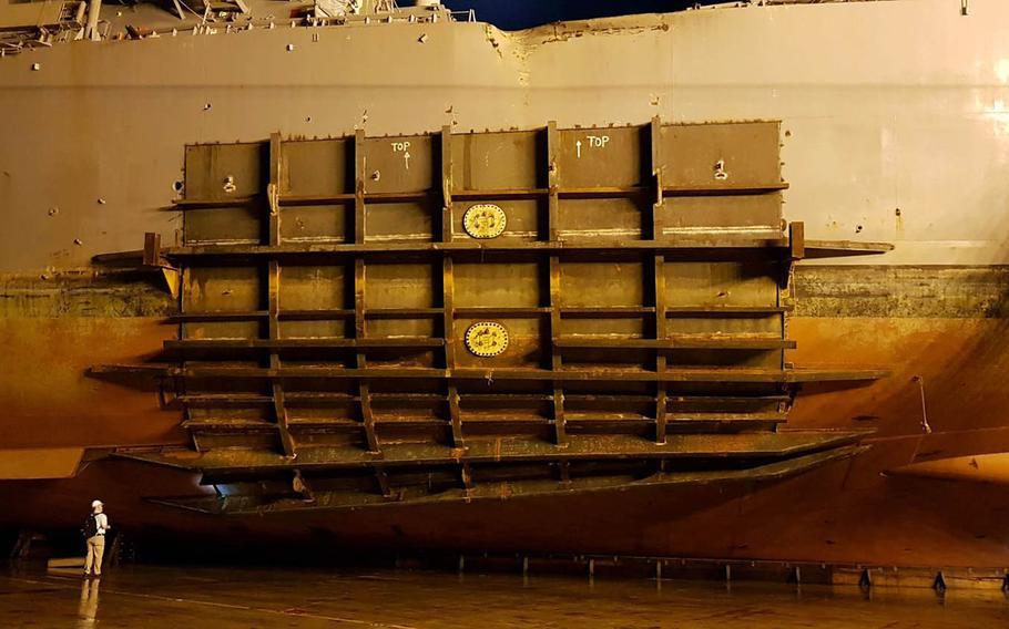 The collision-damaged USS John S. McCain is loaded onto a heavy-lift transport vessel for its return trip to Yokosuka Naval Base, Japan, Oct. 6, 2017.