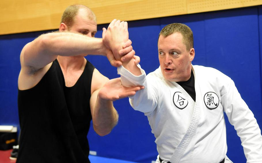 Pfc. Nikolas Petrosyan, left, practices an aikido move on base chaplain Maj. Kevin Hovan during an aikido class at Grafenwoehr, Germany, Tuesday, Oct. 24, 2017.