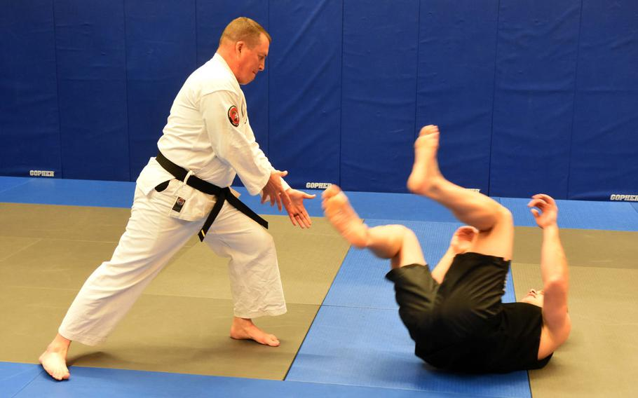 Base chaplain Maj. Kevin Hovan, left, throws Pfc. Nikolas Petrosyan to the ground during an aikido class at Grafenwoehr, Germany, Tuesday, Oct. 24, 2017.