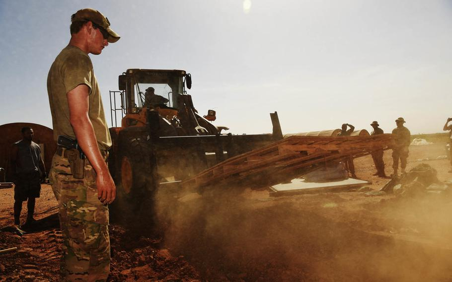 Airmen from the 724th Expeditionary Air Base Squadron and soldiers from the 411th Military Police Company tear up wooden pallets during a move to a new location at Air Base 201, Agadez, Niger, Sept. 11, 2017.