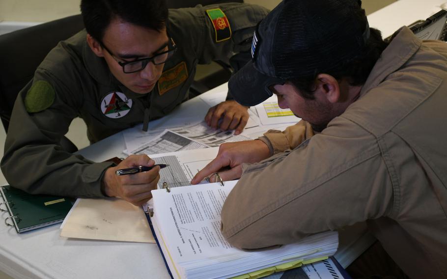 Capt. Jawad Saqib, a trainee UH-60 pilot, studies with an American instructor at Kandahar Air Field, Afghanistan, on Sunday, Nov. 5, 2017.