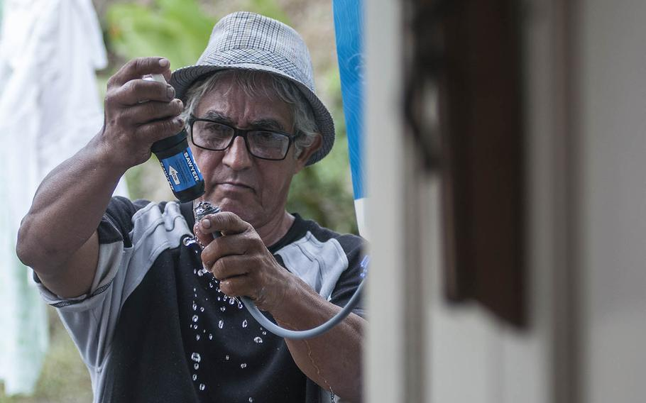 After getting a demonstration from a Red Cross team on how to use a water purifying system, Manuel Febo gives it a try at the home of Carmen Febo in Camerio, Puerto Rico, on Thursday, Nov. 9, 2017.
