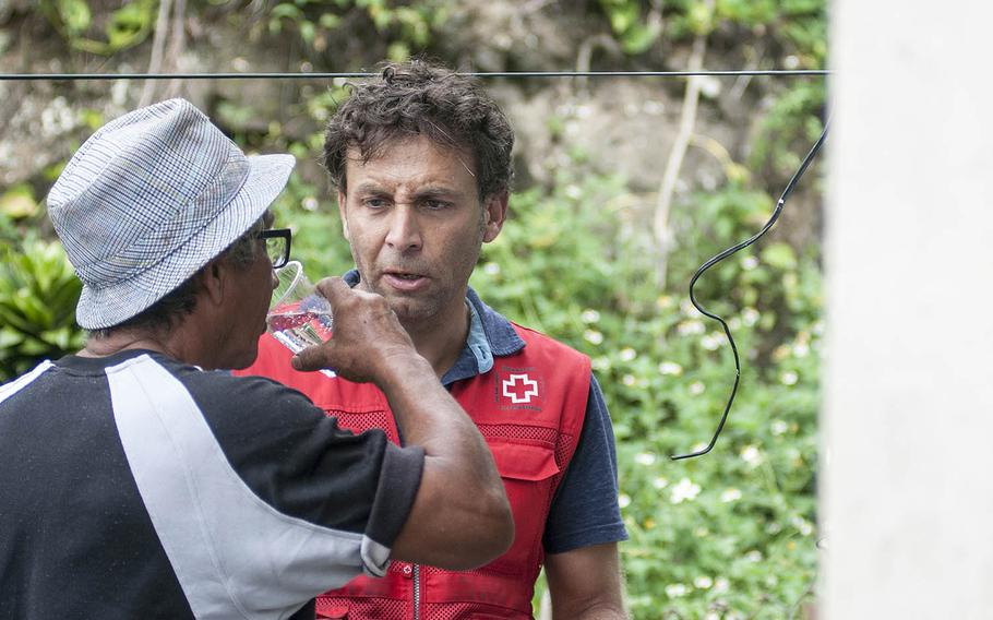 Leandro Taraborrelli, a Red Cross volunteer, watches as Manuel Febo tries freshly filtered water at the home of Carmen Febo in Camerio, Puerto Rico, on Thursday, Nov. 9, 2017.