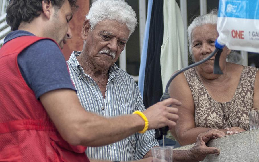 Hector Bueno and wife Nelly Gonzales watch as Red Cross volunteer Leandro Taraborrelli demonstrates how to use a water purifying system at the couple's house  in Camerio, Puerto Rico, on Thursday, Nov. 9, 2017.