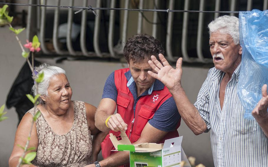 Hector Bueno expresses amazement as his wife Nelly Gonzales looks on as Red Cross volunteer Leandro Taraborrelli demonstrates how to use a solar-powered lamp  at the couple's house  in Camerio, Puerto Rico, on Thursday, Nov. 9, 2017.