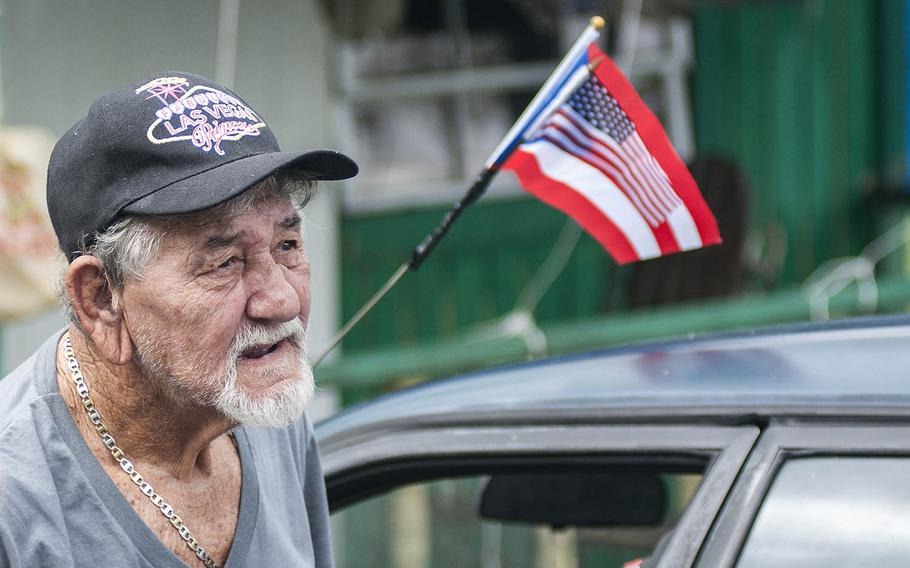 Juan Escribano talks with Red Cross team members on Thursday, Nov. 9, 2017, about the hardships and mental duress he has faced after Hurricane Maria slammed into Puerto Rico in September 2017. Attached to a car in front of his home in Camerio is a small American flag placed atop a Puerto Rican flag.