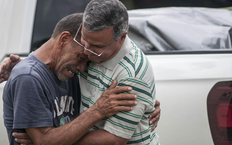 Marco Hernandez, a local pastor acting as guide for a Red Cross team visiting the Comerio region of Puerto Rico. comforts Felix Rodriguez with a long hug on Thursday, Nov. 9, 2017.