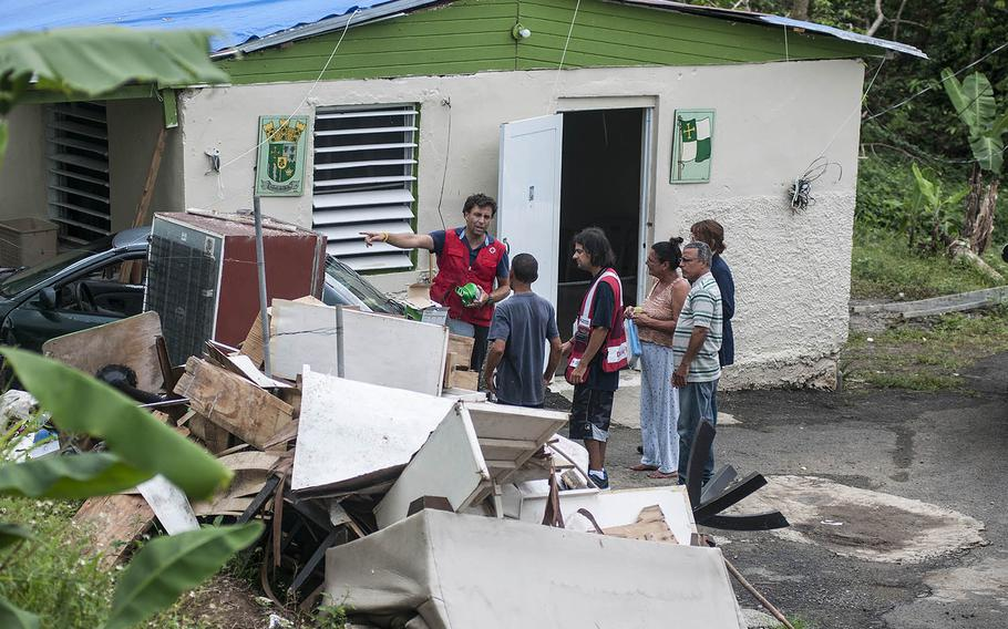 A pile of hurricane damaged belongings sit in front of Margie Ortiz's home, on Thursday, Nov. 9, 2017, as a team of Red Cross volunteers pay a visit while distributing water purifiers and solar-powered lamps to residents in the Comerio region of Puerto Rico.