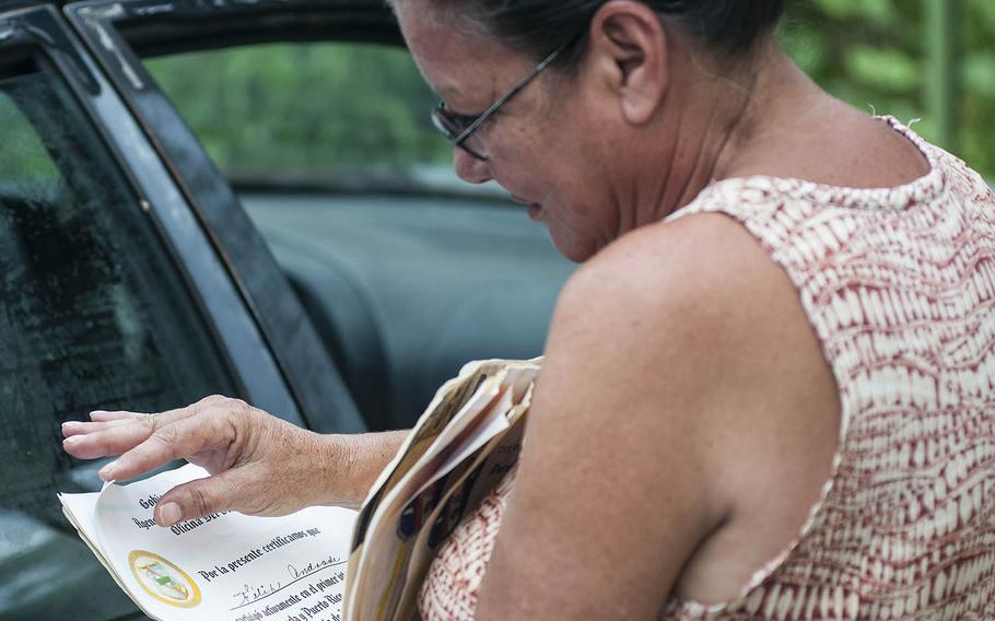 Margie Ortiz looks through important documents on Thursday, Nov. 9, 2017. The papers were salvaged from her residence which was flooded during and after Hurricane Maria slammed into Puerto Rico in September 2017. She keeps the papers in a car parked in front of her home in the Comerio region of Puerto Rico.