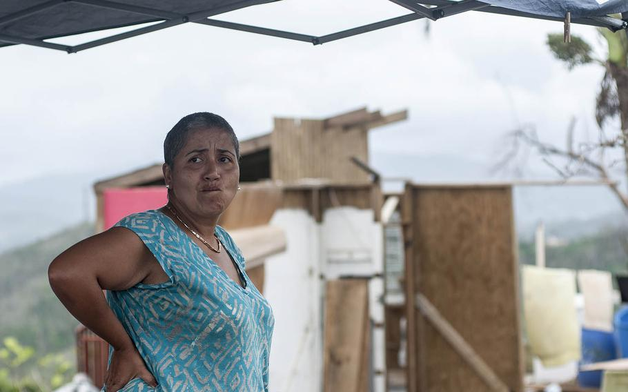 Margaret de Jesus looks out from a small home next to her destroyed dwelling seen in the background in the Comerio region of Puerto Rico, on Thursday, Nov. 9, 2017.