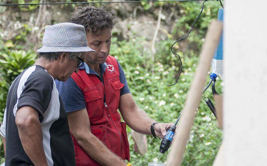 Leandro Taraborrelli, a Red Cross volunteer, shows  Manuel Febo how to use a water purifying system at the home of Carmen Febo in Camerio, Puerto Rico, on Thursday, Nov. 9, 2017.