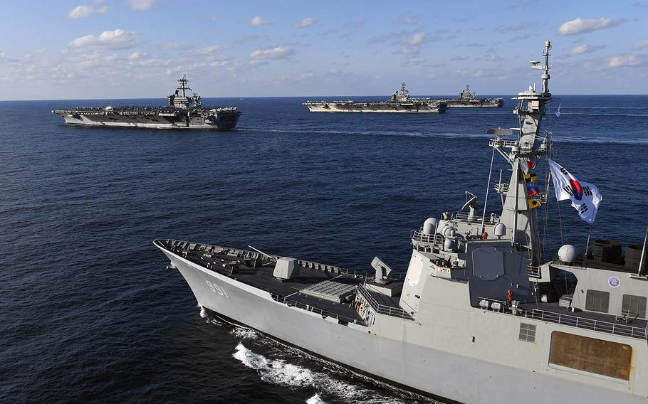 A South Korean navy ship steams alongside the aircraft carriers USS Theodore Roosevelt, USS Ronald Reagan and USS Nimitz during drills east of the Korean Peninsula, Sunday, Nov. 12, 2017.