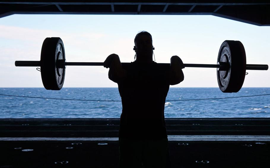 Marine Maj. Jarrod DeVore, executive officer of Marine Fighter Attack Squadron 323, lifts weights on the hangar deck of the aircraft carrier USS Nimitz during a rare break in the intense operations tempo of the Navy's tri-carrier exercise near the Korean Peninsula, Monday, Nov. 13, 2017.
