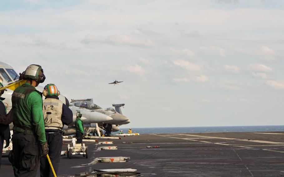 Green-shirted hook-runners, who ensure the arresting cable is reset for each aircraft, wait for a jet to land on the USS Nimitz during a rare tri-carrier exercise near the Korean Peninsula, Monday, Nov. 13, 2017.