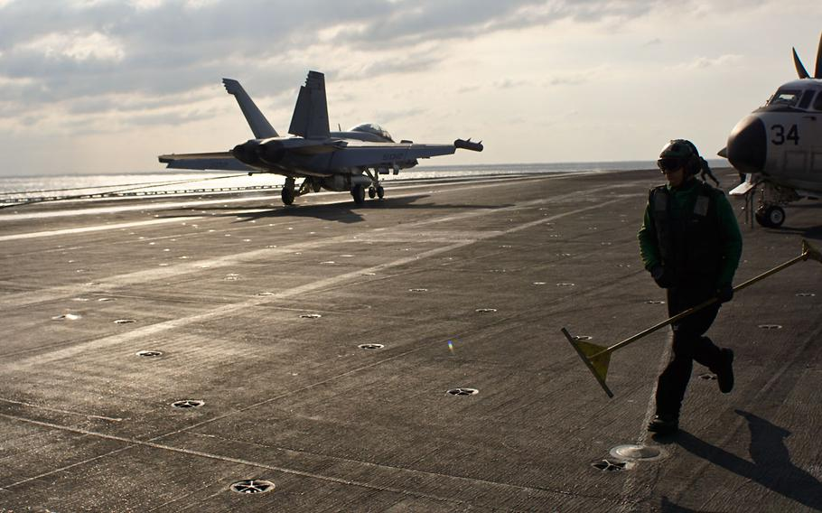 A hook-runner rushes to reset the arresting cable for another plane to land on the flight deck of the carrier USS Nimitz during the Navy's tri-carrier exercise in the Sea of Japan, Monday, Nov. 13, 2017.