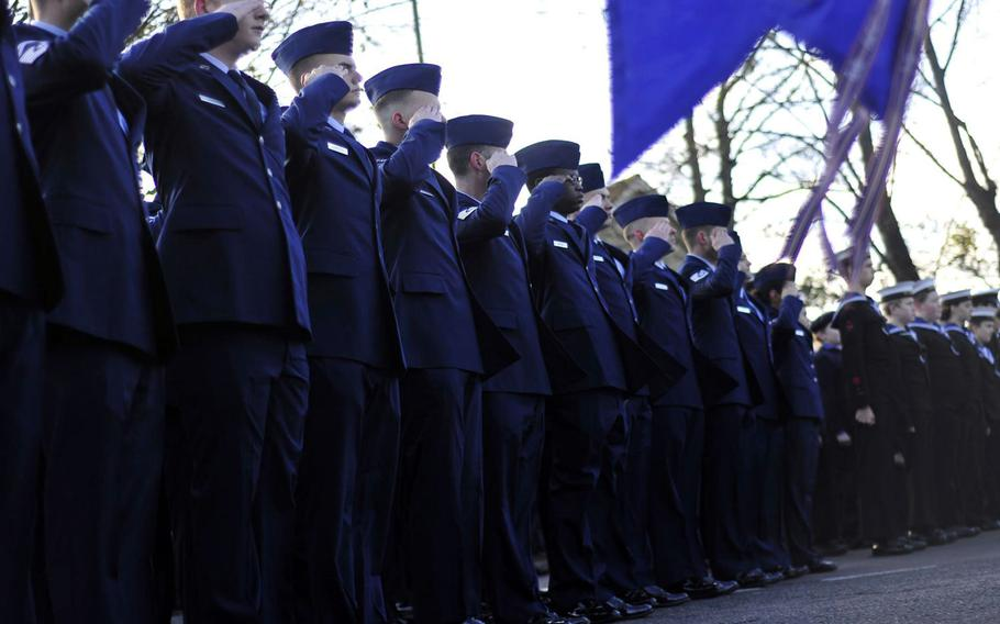 An airman first class, sixth from left, stands and salutes with others in formation during the playing of the British and American national anthems at a Remembrance Day ceremony in Mildenhall, England, on Sunday, Nov. 12, 2017. He later fell out and took a knee during reveille. Service officials said he was feeling faint, rather than protesting, following a flurry of angry comments on social media.