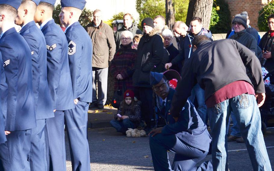 An airman, while part of a ceremonial detail from RAF Mildenhall, stepped out of the formation and took a knee when the music to reveille began playing during a Remembrance Day ceremony in Mildenhall, England, on Sunday, Nov. 12, 2017. Air Force officials said the airman felt faint, but others on social media interpreted the photo as a protest. The airman previously stood and saluted during the U.S. and British national anthems.