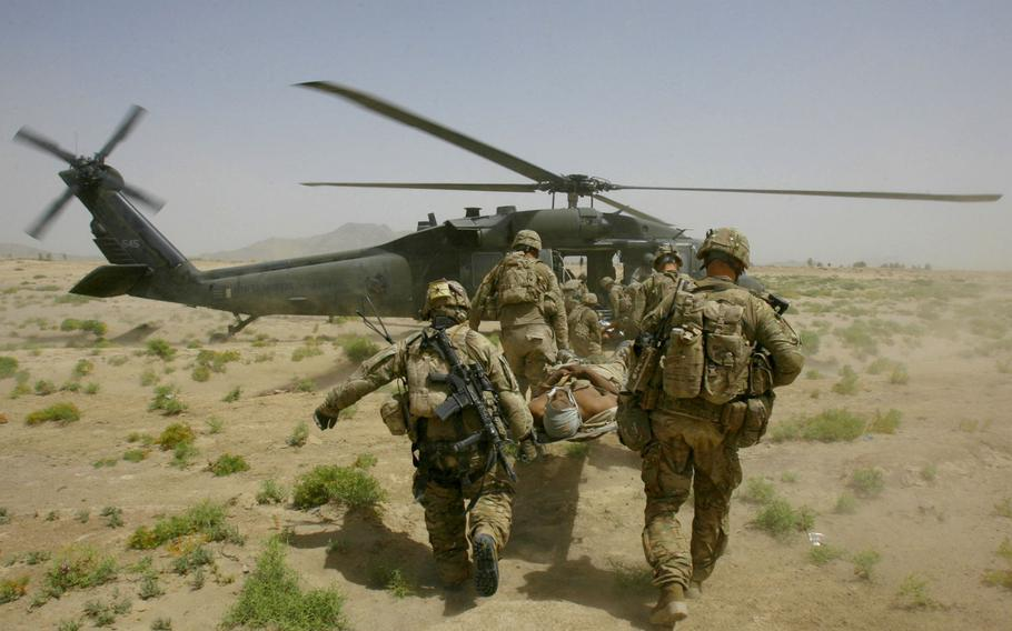 A soldier is evacuated to a medevac helicopter after being injured in an improvised explosive device attack near Molla Dust in Kandahar province, Afghanistan, on June 15, 2011.