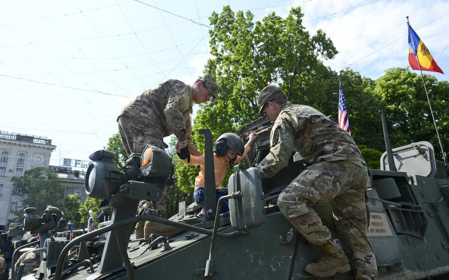 U.S. Army soldiers of the Regimental Engineer Squadron, 2nd Cavalry Regiment, stationed out of Grafenwoehr, Germany, help a young boy get inside a Styker during a static display in Chisinau, Moldova, May 8, 2016. NATO is set to open a new security cooperation center in the country.