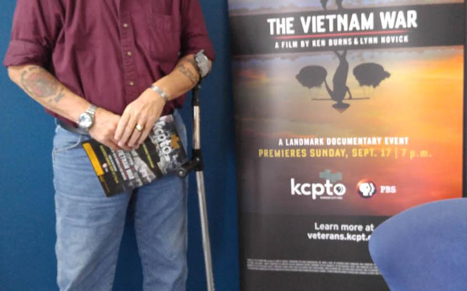 """Vietnam veteran and poet John Musgrave stands in front of the poster for """"The Vietnam War"""" documentary, in which he is featured, during a Kansas preview ahead of the film's airing on PBS in September.  Musgrave overcame severe post-traumatic stress after being shot  in the face and chest in November 1967, sustaining life-threatening and permanently disabling injuries, and now helps to counsel post-911 veterans.  Photo courtesy of John Musgrave"""