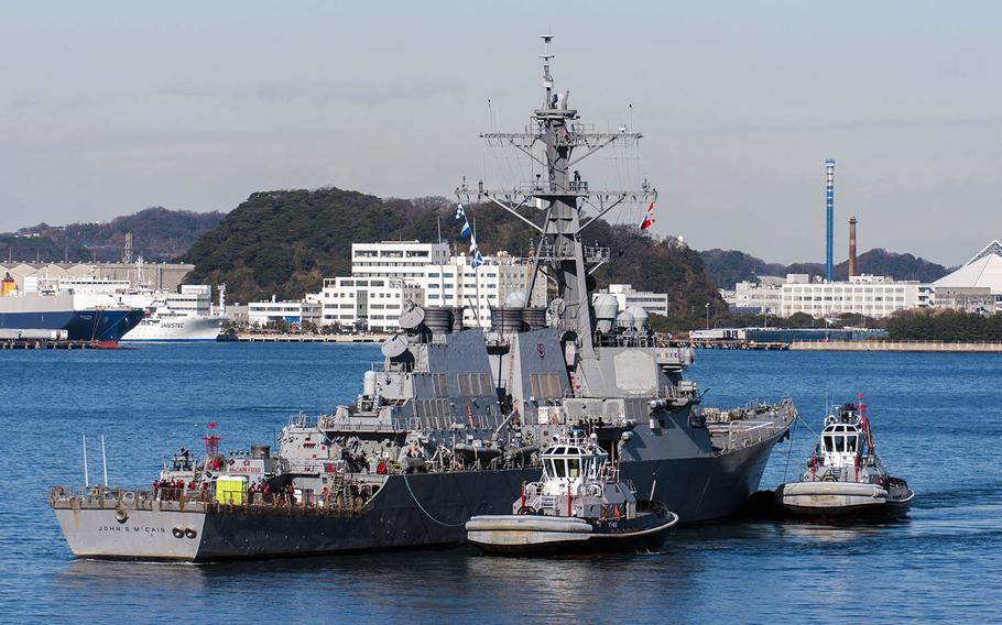 The guided-missile destroyer USS John S. McCain is towed to the pier at Yokosuka Naval Base, Japan, Wednesday, Dec. 13, 2017.