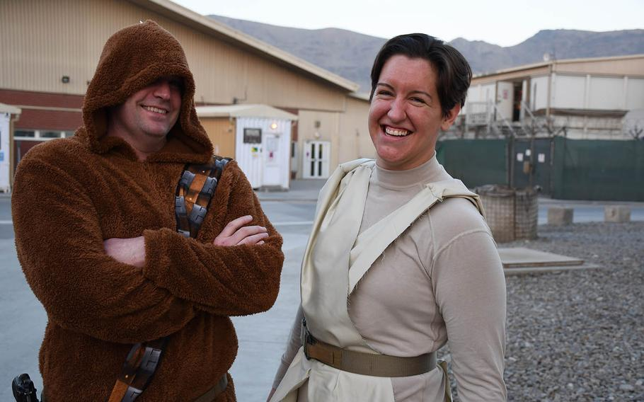 """Air Force Maj. Patrick Currie, left, dressed in a Chewbacca outfit his wife sent him, and Capt. Madison Scaccia, in a Rey costume she made out of issued gear and a swatch of cloth from the base bazaar, wait in line for a for a screening of """"Star Wars: The Last Jedi"""" at a coalition base in Kabul, Afghanistan, on Saturday, Dec. 23, 2017."""