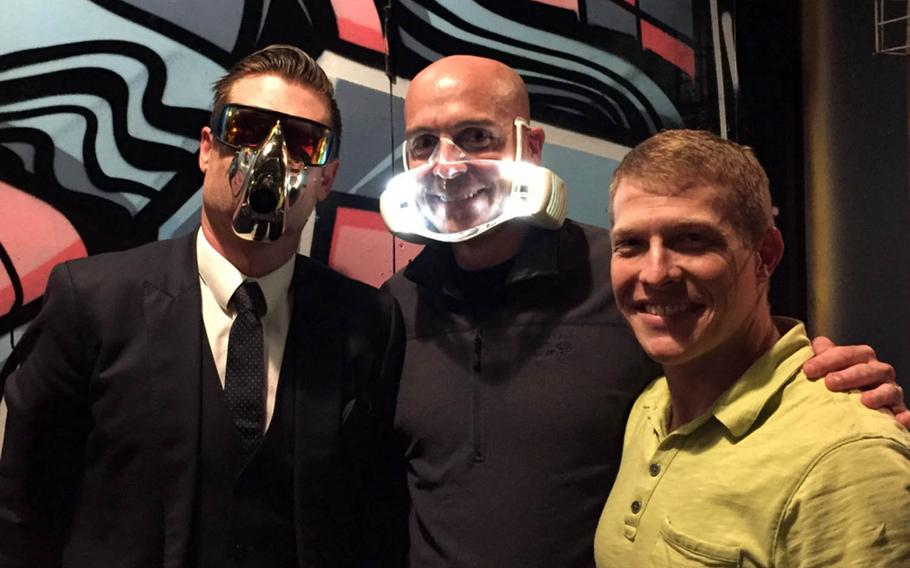 Dan Bowden, left, CEO of the high-tech startup O2O2, and Cmdr. Tom Ogden don prototype facemasks the company is developing in Auckland, New Zealand.  Lt. Cmdr. Derek Fletcher, right, recently spent five weeks at the company evaluating the product's potential uses on Navy flight decks.