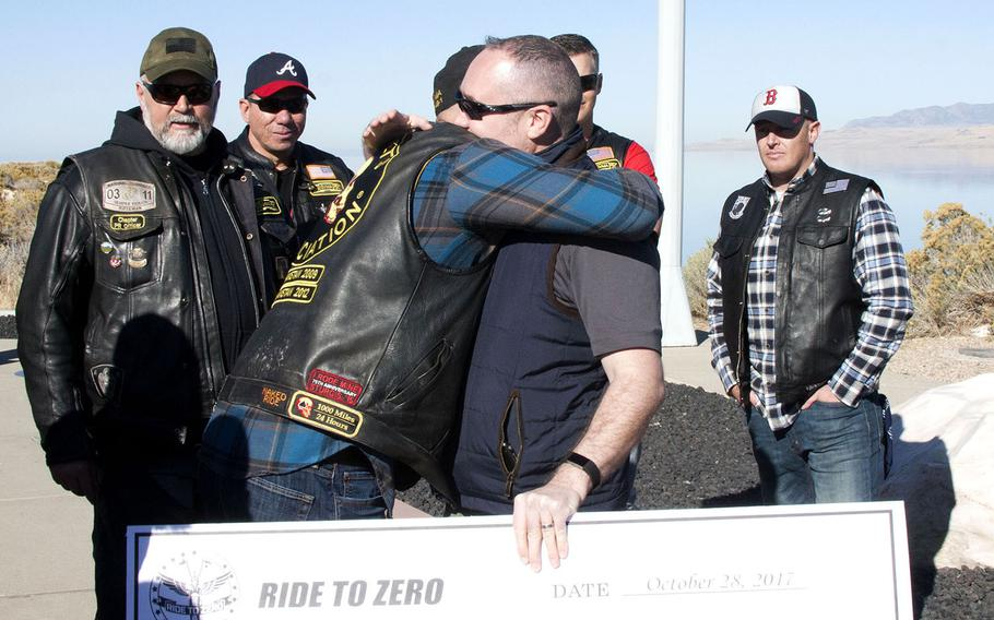 Ryan Fleischman, a member of the Combat Veterans Motorcycle Association, hugs psychologist Craig Bryan after awarding Bryan and the National Center for Veterans Studies $35,000 for suicide prevention. The association concluded its annual Ride to Zero initiative Saturday, Oct. 28 at Antelope Island State Park in Utah.
