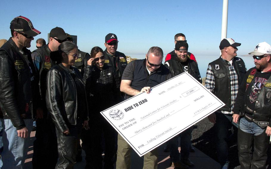 Craig Bryan, a veteran and psychologist leading the National Center for Veterans Studies, holds a check given to him Saturday, Oct. 28, by the Combat Veterans Motorcycle Association at Antelope Island State Park in Utah. The money will go toward suicide-prevention research.